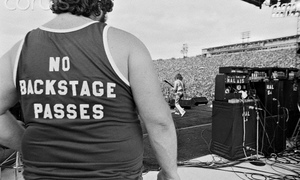 A roadie guards a stage in the 1970s.